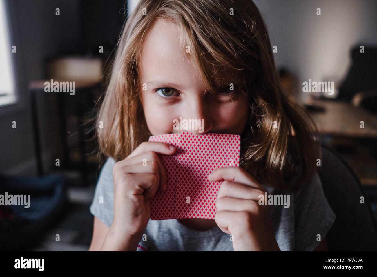 Bambina che si nasconde dietro le carte da gioco in soggiorno, ritratto Immagini Stock
