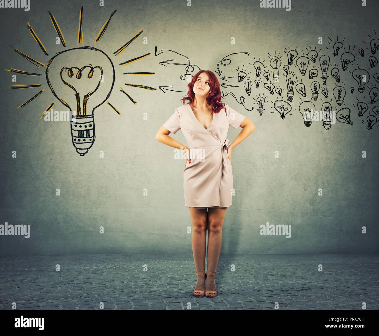 A piena lunghezza Ritratto di un rosso giovane donna in piedi con le mani sui fianchi cercando di pensare positivo. Il concetto di Business pensieroso ragazza raccogliere le idee Immagini Stock