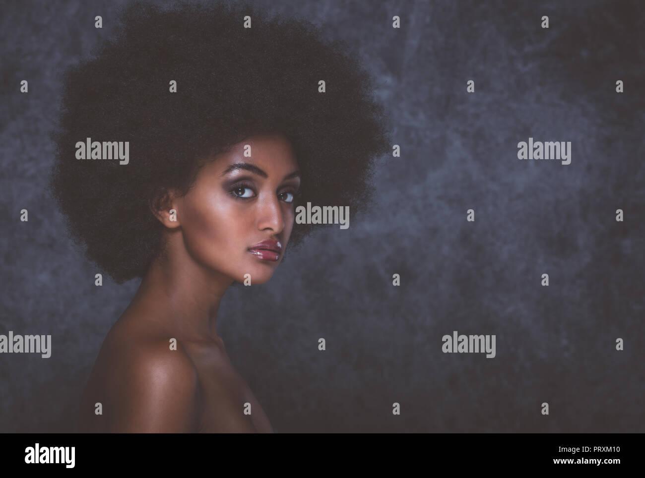 Foto circa Bella donna nera con capelli ricci lussuosi.