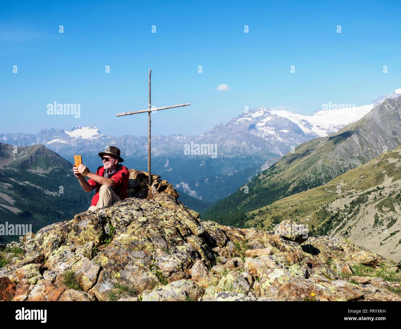 Lombardia, Passo di Val Viola, uomo di scattare le foto con il suo smartphone, seduti al vertice di croce Immagini Stock