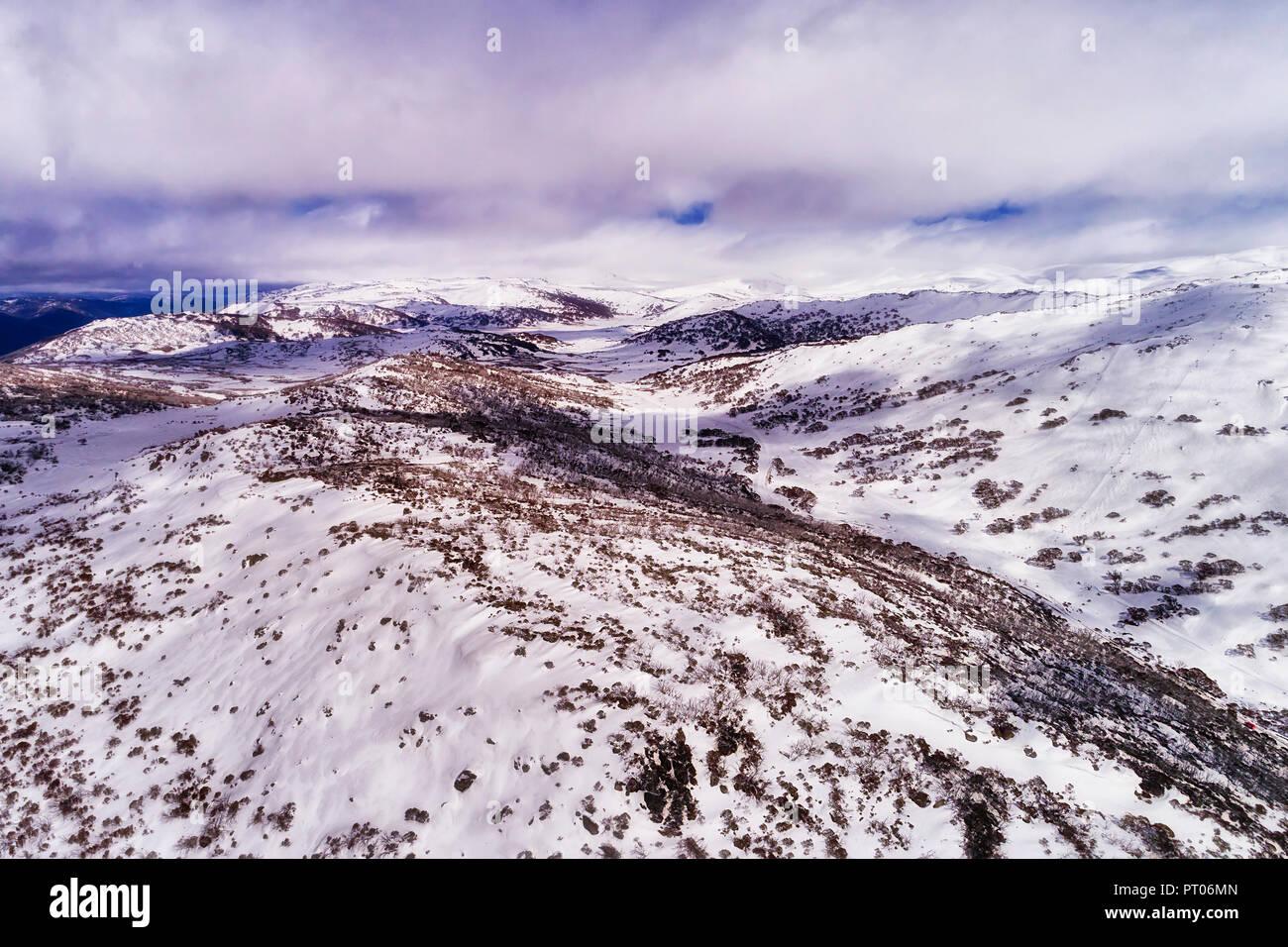 Il bianco della neve pendii delle montagne più alte in Australia sotto nuvole bianche lungo Perisher valley con neve spessa e stazione sciistica piste sportive. Immagini Stock
