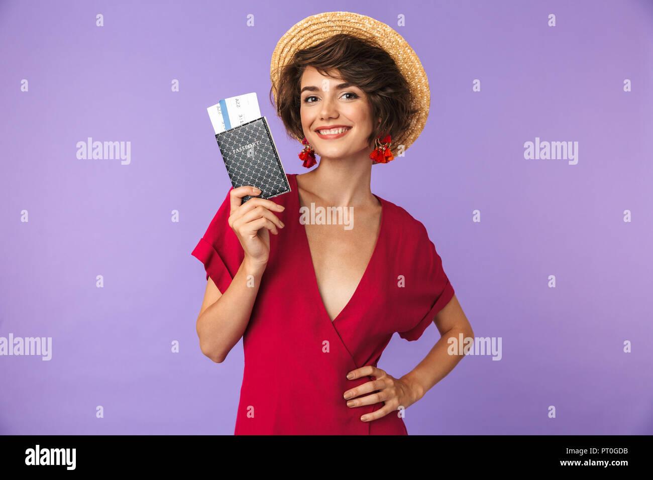 ... giovane donna 20s indossando grande cappello di paglia sorridenti  mentre si tiene il passaporto e i biglietti di viaggio isolate su sfondo  bianco 52bde355f72f
