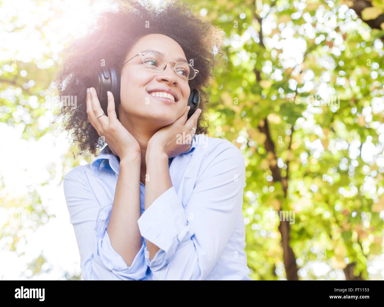 Ritratto di Bella felice Afro American giovane donna ascolto di musica con cuffie in natura, attraente razza mista femmina di divertimento all'aperto Foto Stock