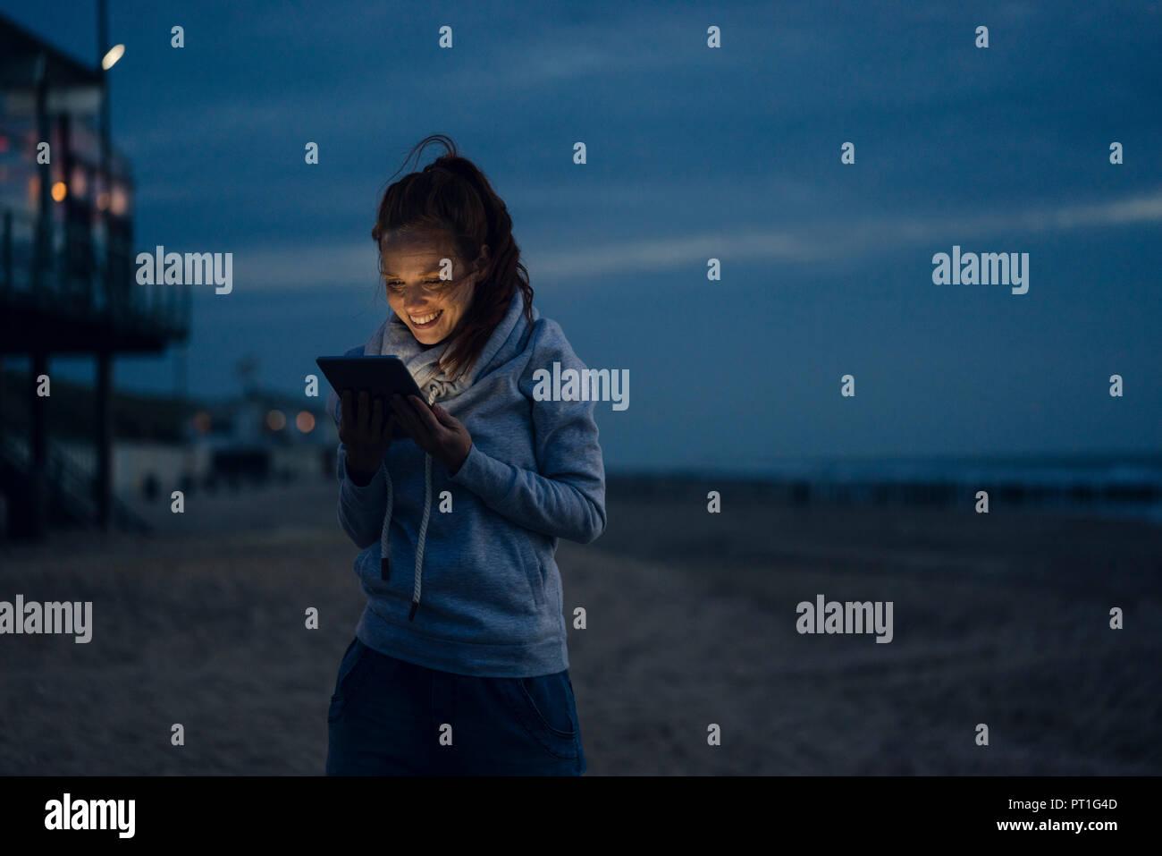 Donna con tavoletta digitale sulla spiaggia al tramonto Foto Stock