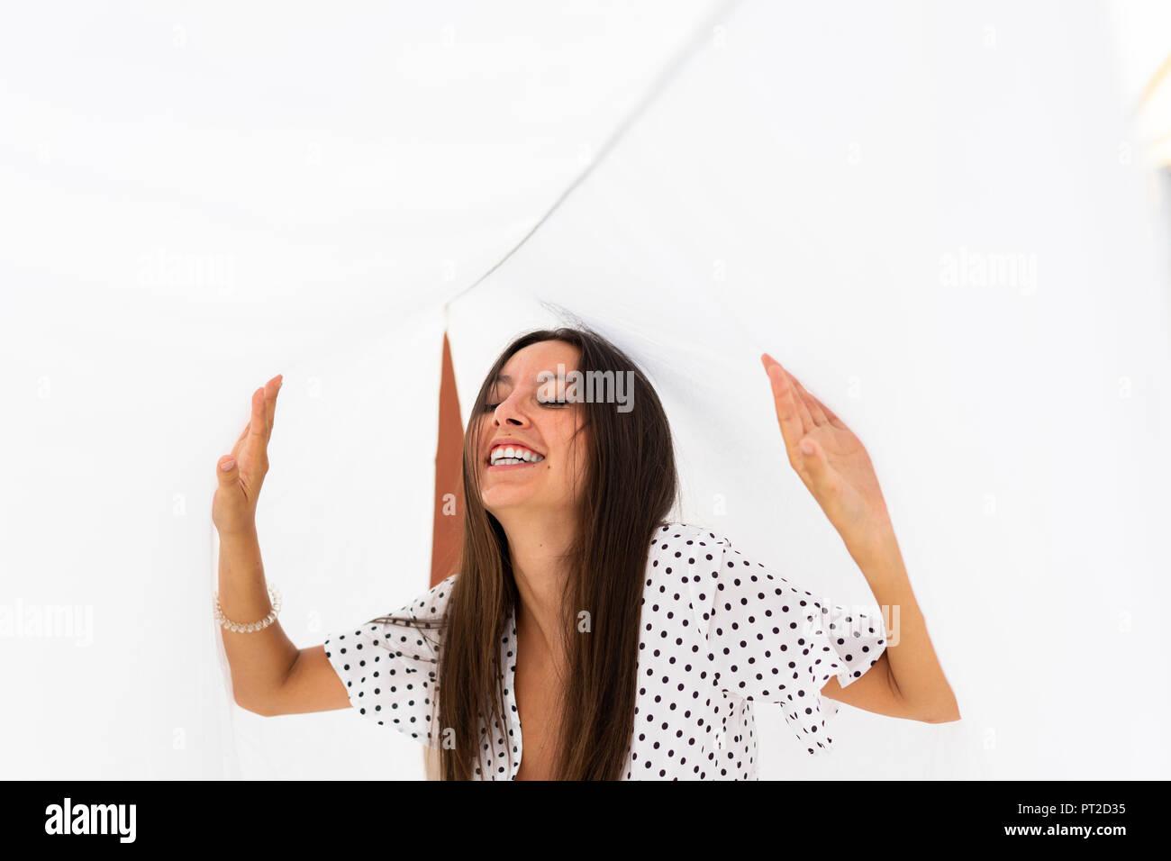 Ritratto di ridere giovane donna con il letto di asciugatura fogli sulla terrazza sul tetto Immagini Stock