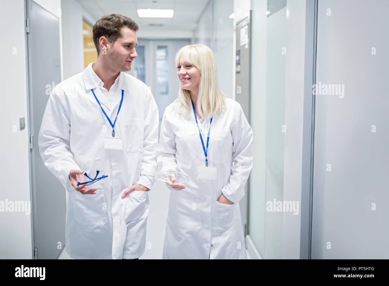Maschio e femmina di dottori in camici camminare in corridoio. Foto Stock