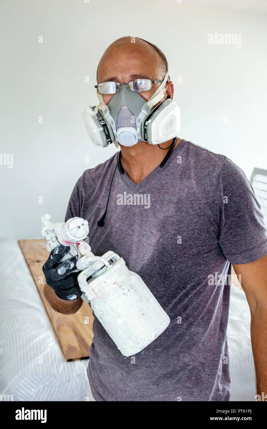 Miami Beach Florida uomo ispanico pittore maschera di lavoro pistola di verniciatura a spruzzo contraente di lavoro Immagini Stock