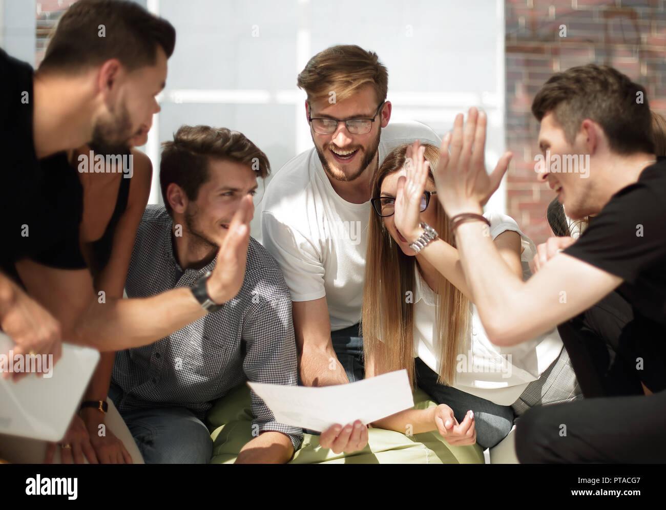 Giovani imprenditori dando a ogni altro un alto cinque in occasione di un incontro informale Immagini Stock