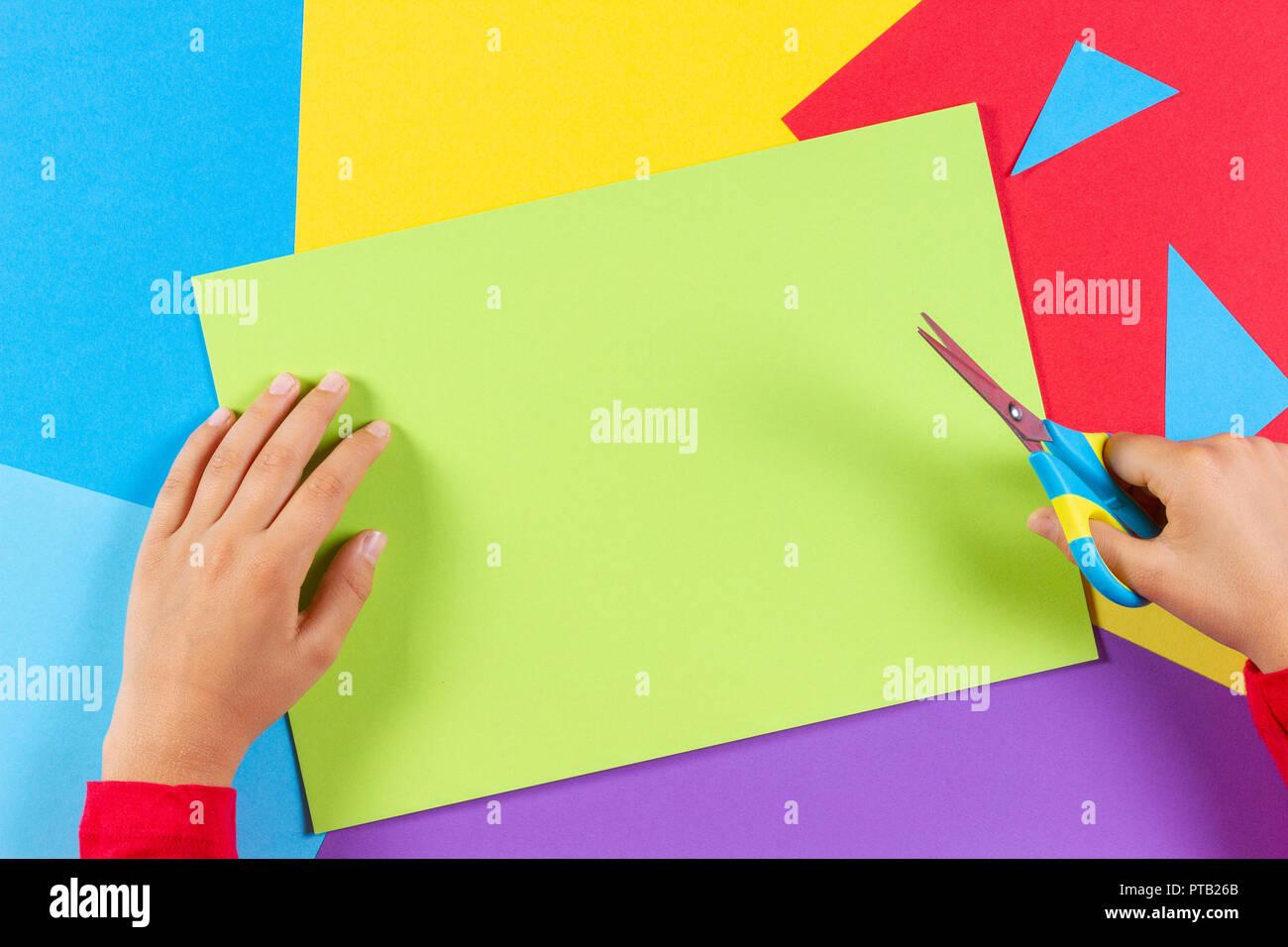 Il capretto con le mani in mano il taglio di carta colorata con le forbici Immagini Stock