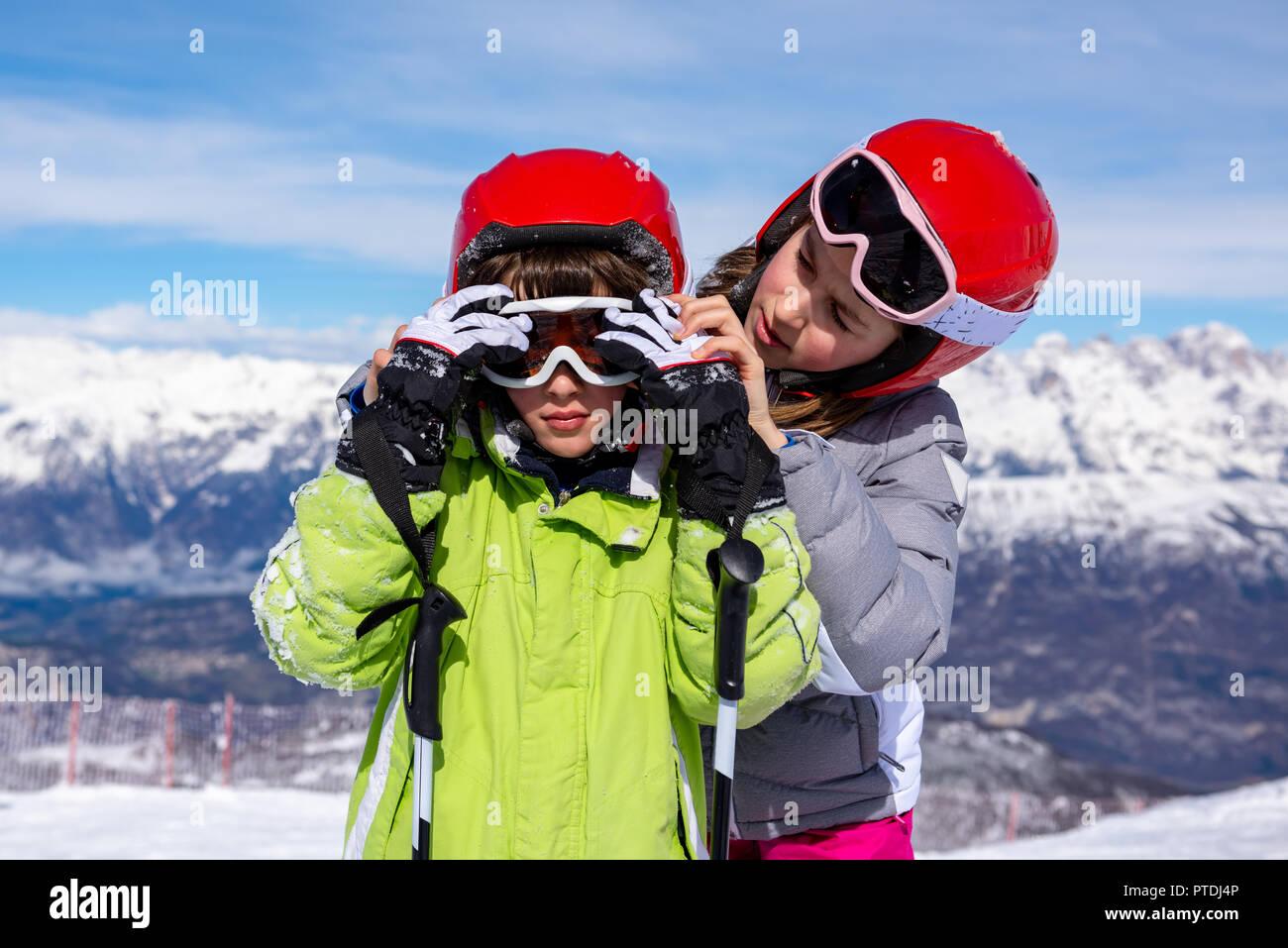Bambina aiuta il bambino ad indossare gli occhiali da sci Immagini Stock