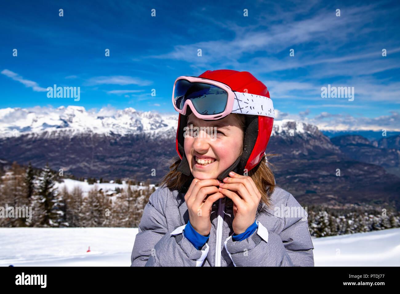 Bambina sulle piste da sci con casco e occhiali da sci Immagini Stock