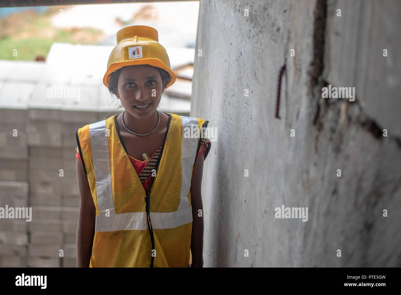 Donna operaio con la sicurezza usura alla costruzione sito. Città Urban in India è vedere un sacco di progetti di sviluppo. Immagini Stock