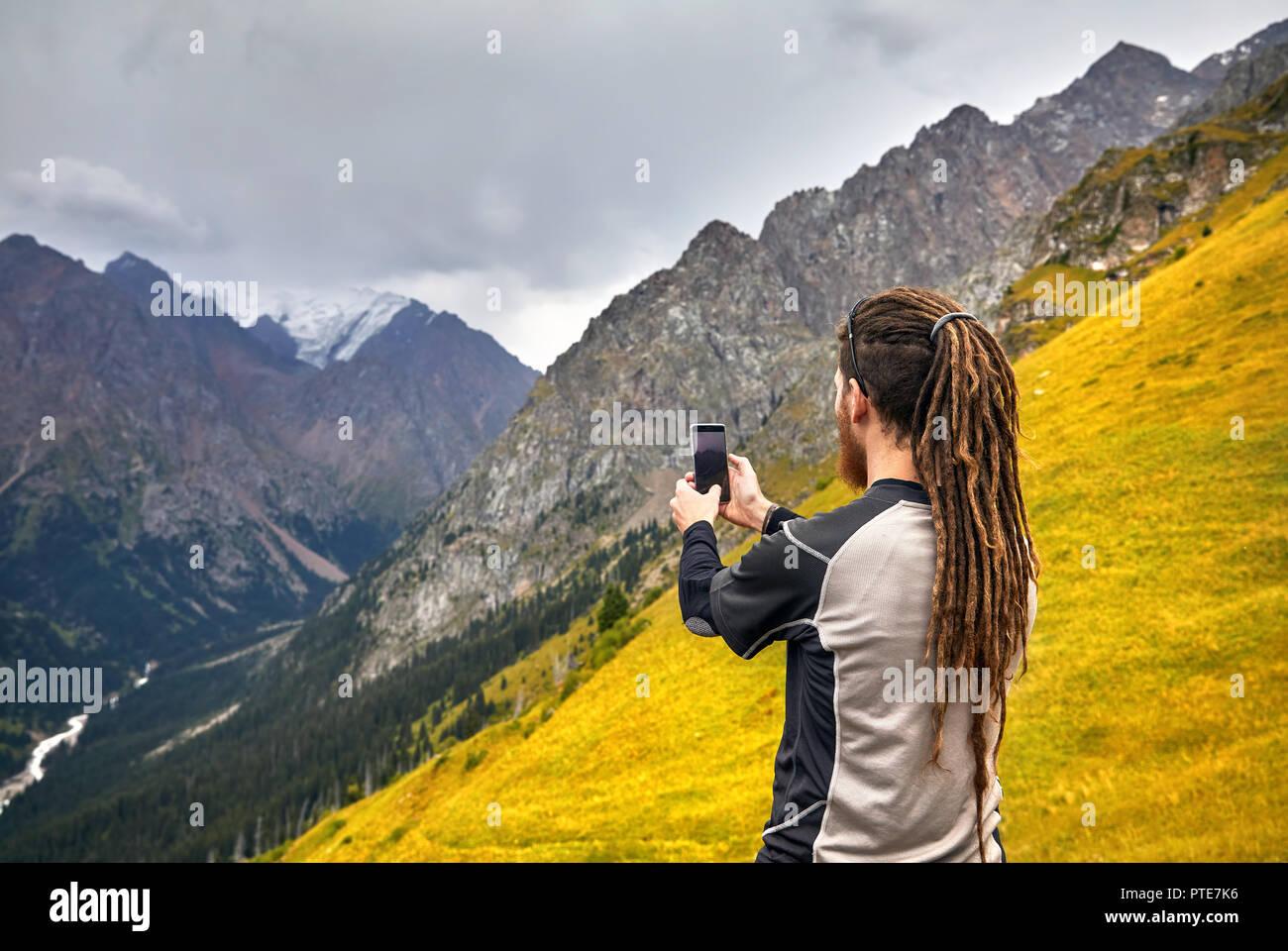Uomo Con Dreadlocks Prendendo Foto Con Il Suo Telefono Cellulare In