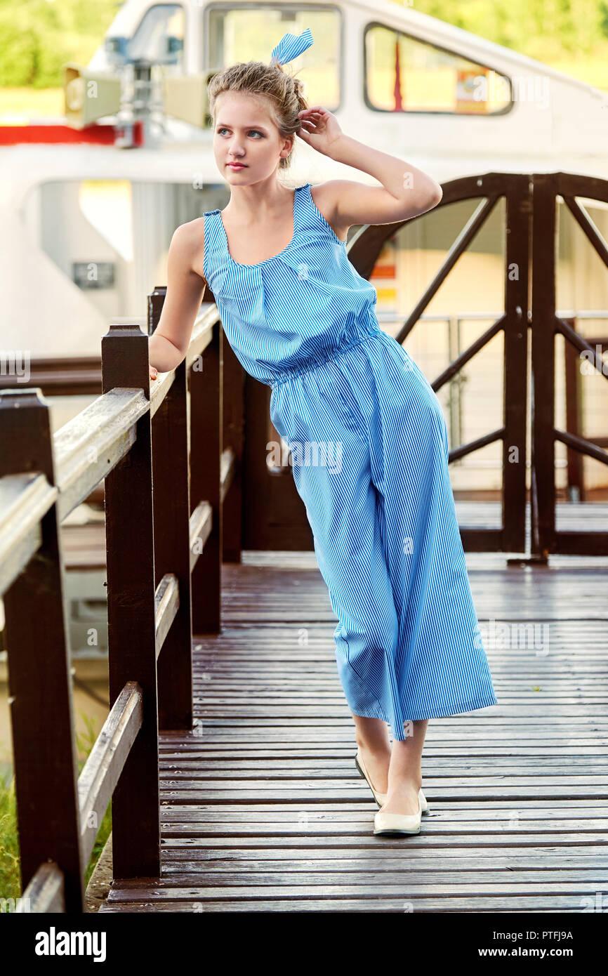 Bellissimo modello in striped costume blu nel suo complesso in stile marino. Lunghezza completa in posa vicino alla ringhiera,pier,ponte. Ragazza indossando eleganti abiti freschi all'esterno. Il concetto di moda. Estate, lifestyle, giorno Immagini Stock