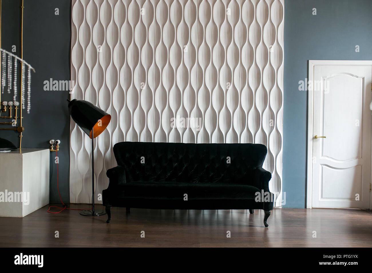 Divano Nero E Bianco : Un divano nero e un nero lampada da terra contro un bianco