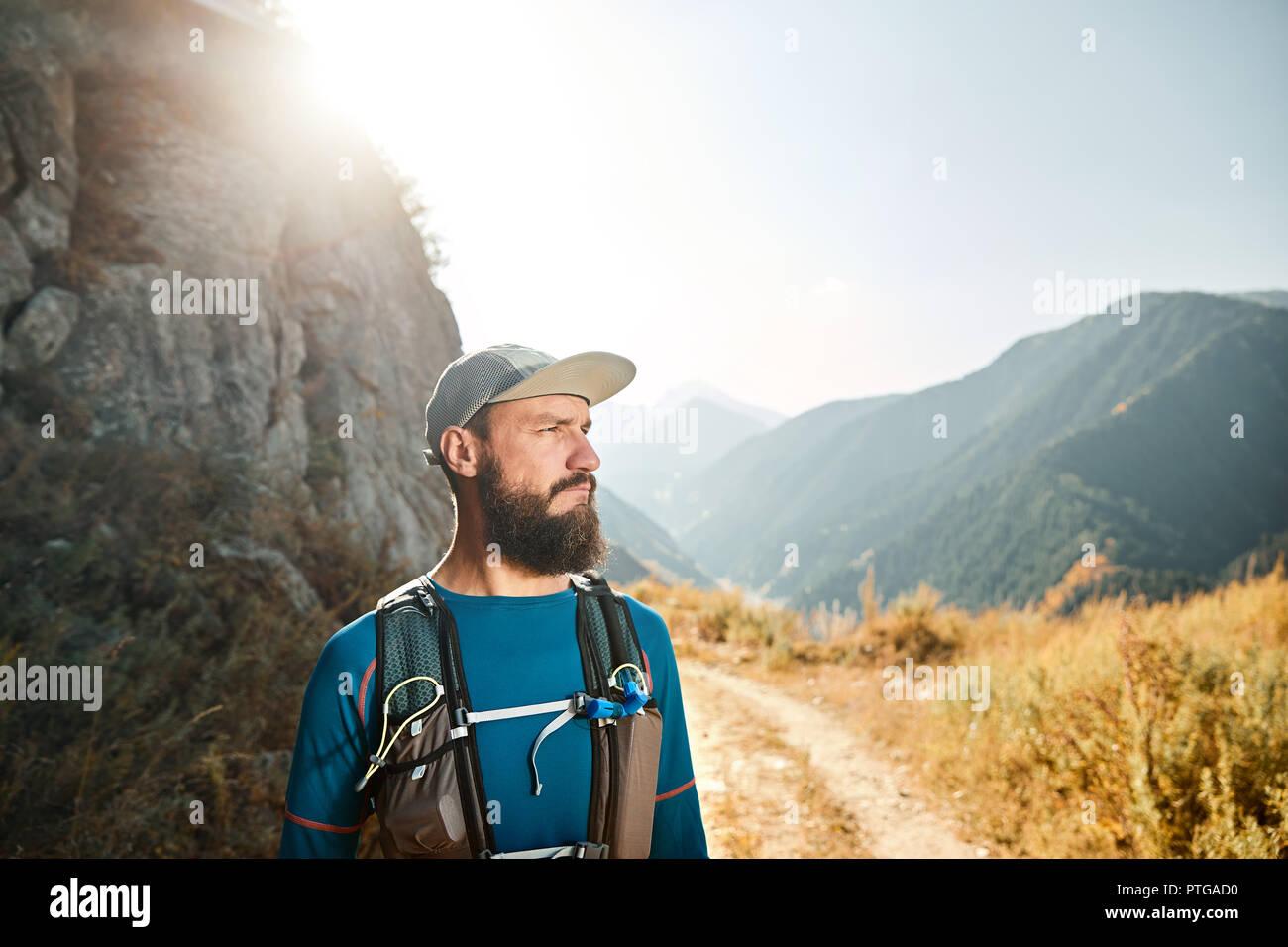 Ritratto di barbuto atleta runner con zaino in montagna a sunrise Immagini Stock