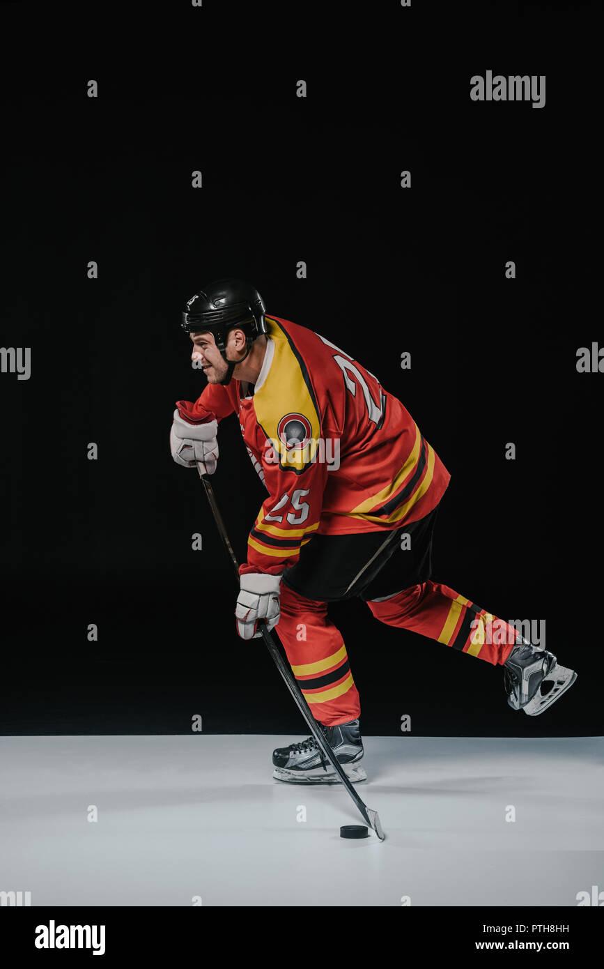 Vista laterale di hockey su ghiaccio giocatore giocare ad hockey e guardando lontano su nero Immagini Stock