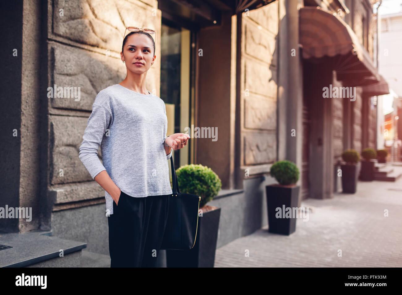 49cd53608e1b Giovane donna camminando sulla strada della citta . Ragazza indossando  abiti eleganti e accessori Immagini