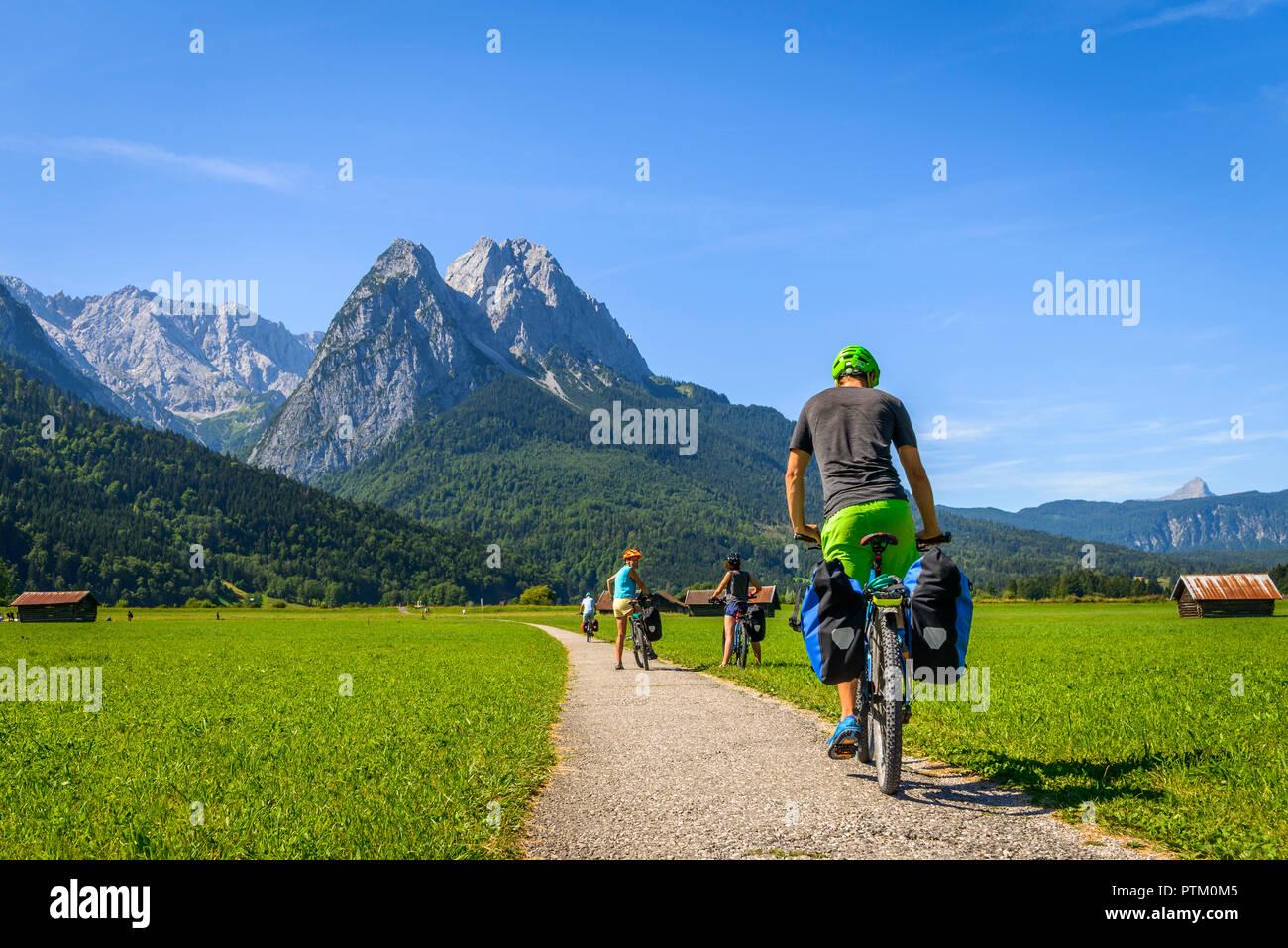 Ciclista sulla Gita in Bicicletta Equitazione sulla pista ciclabile sulla sua mountain bike, nel retro Zugspitze, Tegernauweg, vicino a Grainau Immagini Stock