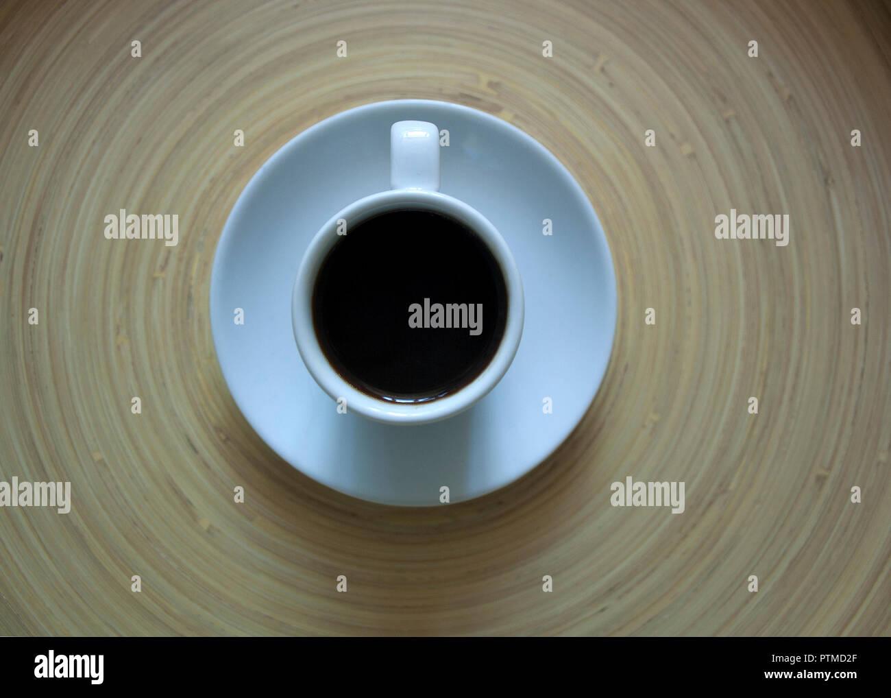 Una tazza di caffè su un sfondo di legno con il design circolare Immagini Stock