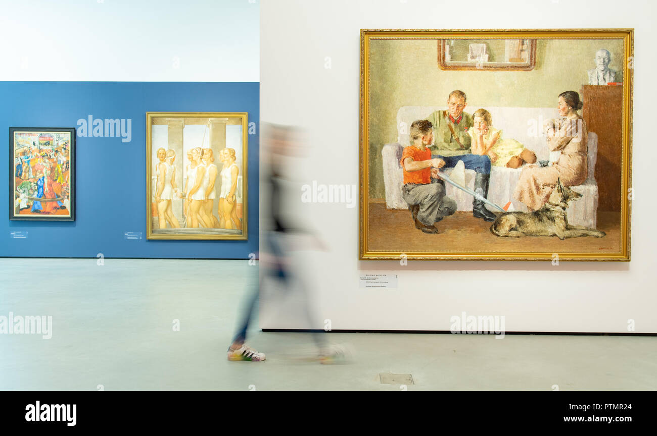 """Il 10 ottobre 2018, Baden-Wuerttemberg, Mannheim: una giovane donna va alla mostra """"costruzione del mondo. Kunst und Ökonomie' alla Kunsthalle di Mannheim, le opere degli artisti Philip Evergood (l-r) con il titolo 'Tanzmarathon"""" (1934), Gerhard Keil con il titolo 'Turnerinnen"""" (1939), e Vladimir Wassilyev con il titolo 'Die Familie des Kommandanten' (1938). Dalla giustapposizione di due epoche, la mostra espone per la prima volta la drammatica influenza di economia sull'arte. Foto: Uwe Anspach/dpa Immagini Stock"""
