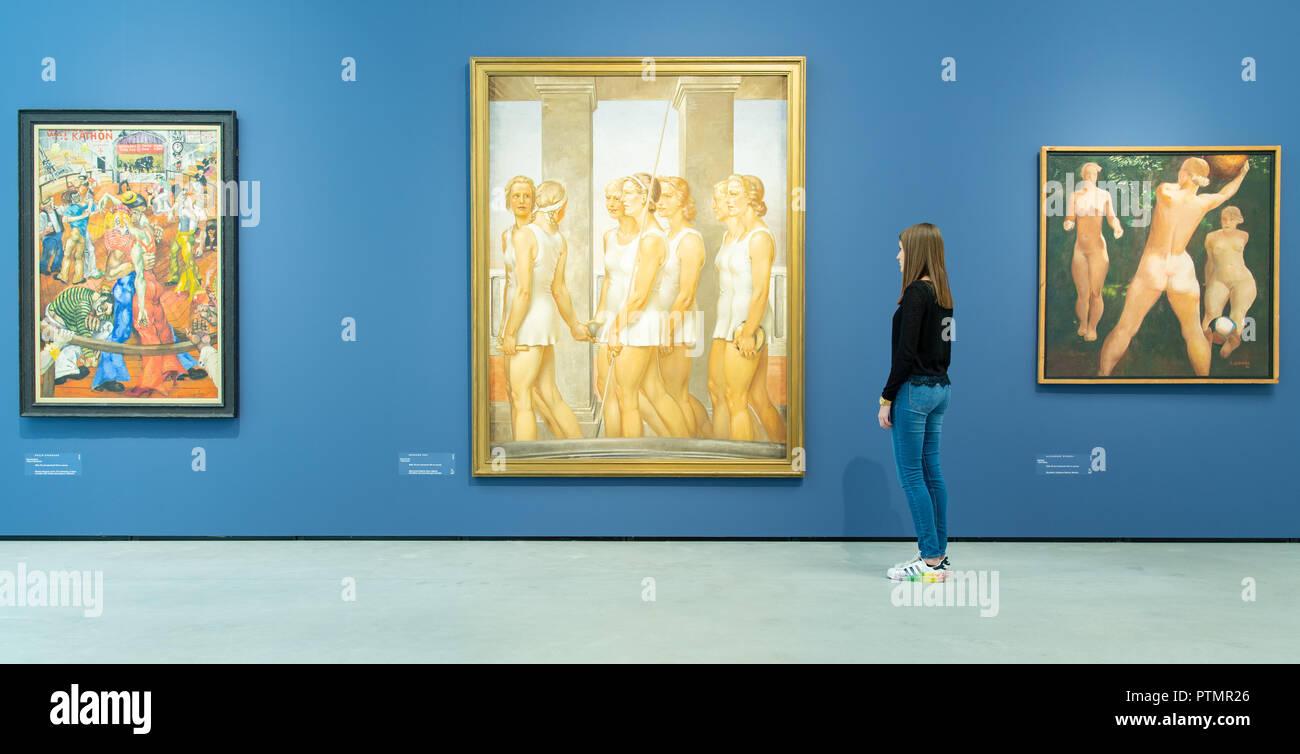 """Il 10 ottobre 2018, Baden-Wuerttemberg, Mannheim: una giovane donna si erge nella mostra """"costruzione del mondo. Kunst und Ökonomie' alla Kunsthalle Mannheim prima di opere degli artisti Philip Evergood (l-r) con il titolo 'Tanzmarathon"""" (1934), Gerhard Keil con il titolo 'Turnerinnen' (1939) e Alexander Deineka con il titolo 'Ballspiel' (1932). Dalla giustapposizione di due epoche, la mostra espone per la prima volta la drammatica influenza di economia sull'arte. Foto: Uwe Anspach/dpa Immagini Stock"""