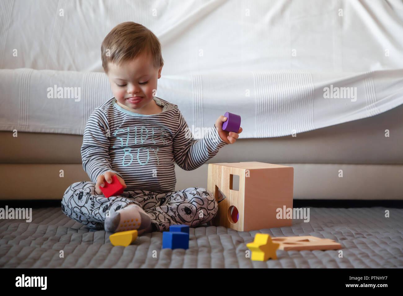 Ritratto di carino ragazzo con la sindrome di Down giocando in casa Immagini Stock