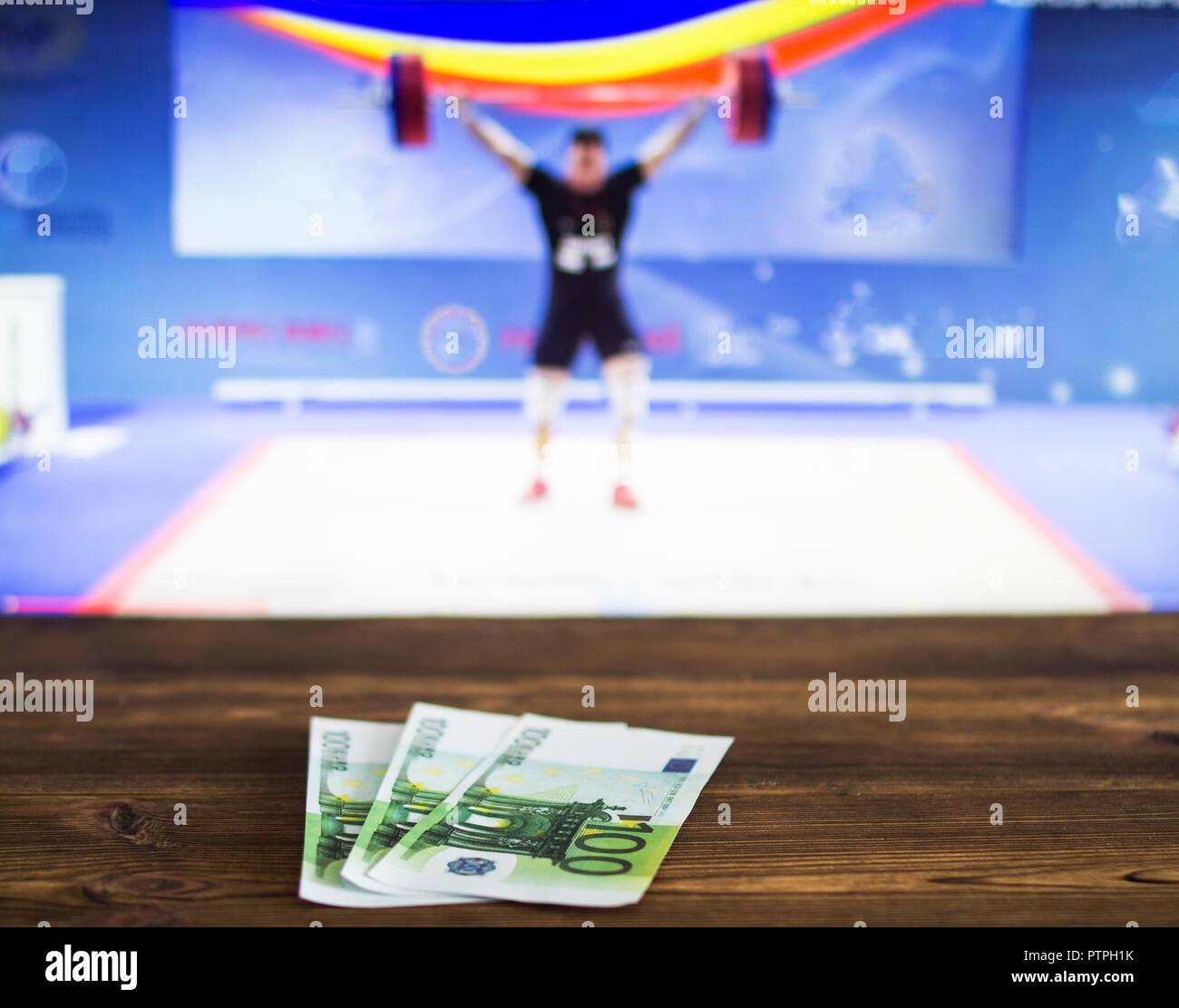 Euro denaro sullo sfondo del televisore su che mostrano il sollevamento pesi, scommesse sportive, bookmaker Immagini Stock