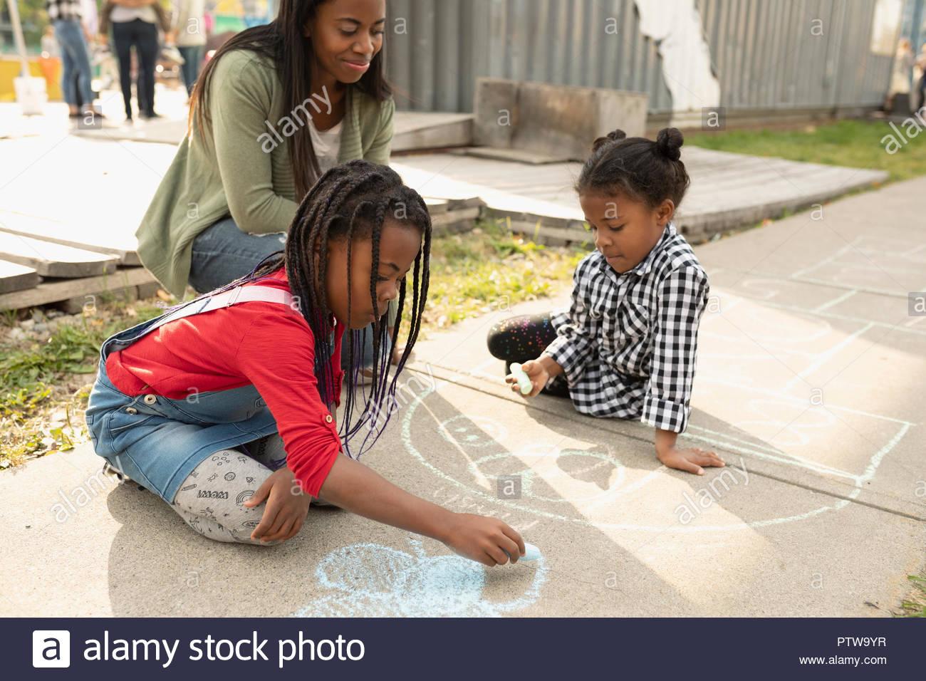 La madre e le figlie di disegno con sidewalk chalk Immagini Stock