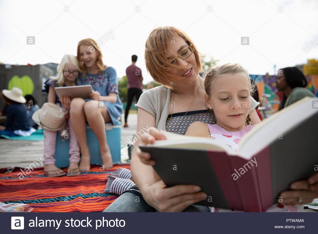 Madre e figlia libro lettura in posizione di parcheggio Immagini Stock