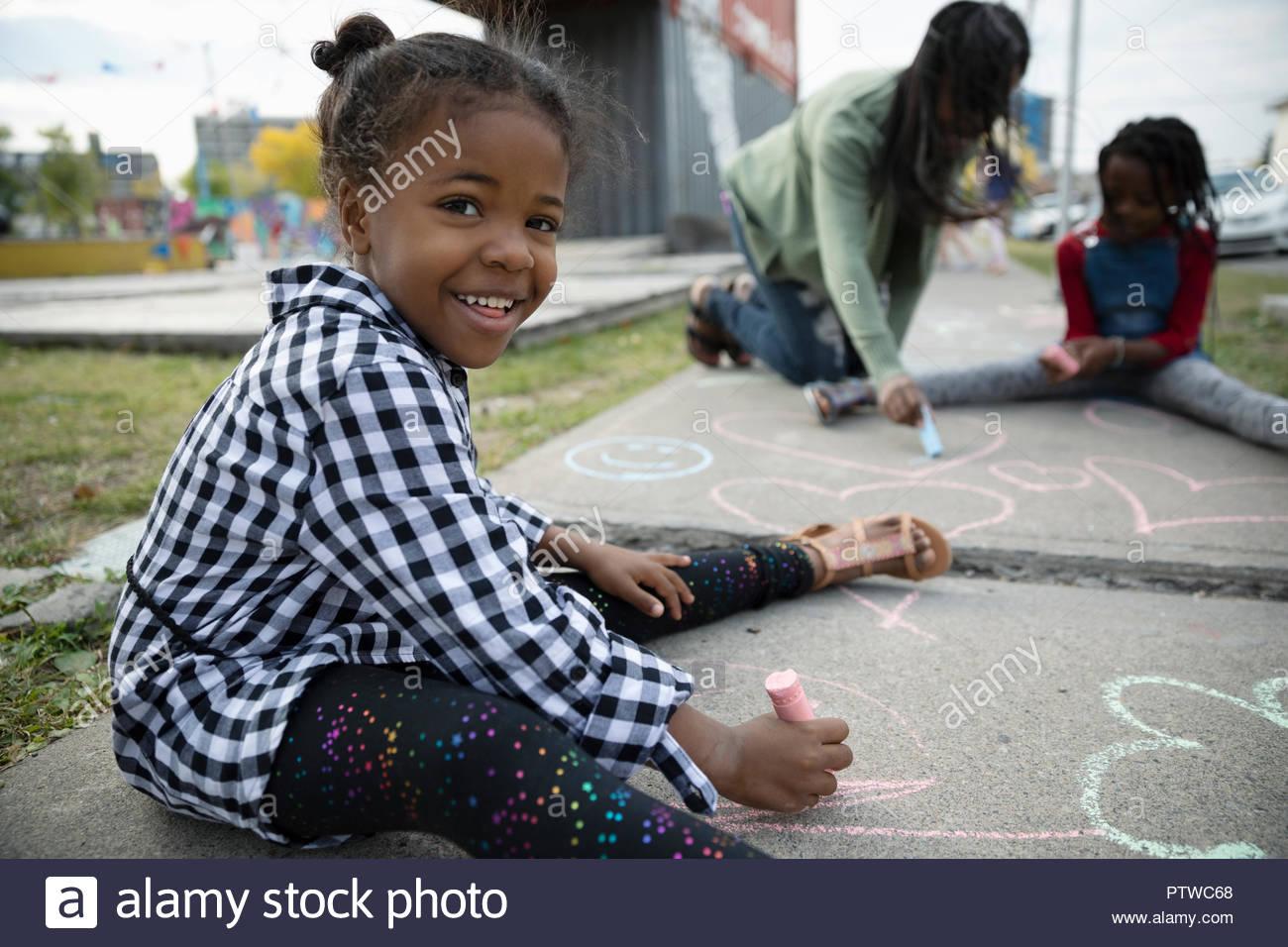 Ritratto sorridente ragazza carina di disegno con sidewalk chalk Immagini Stock