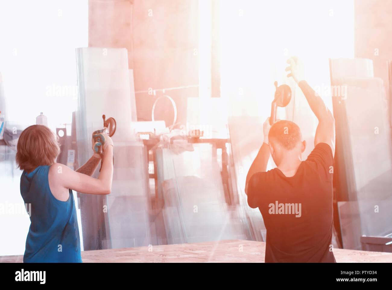 Produzione di finestre in pvc, lavoratori sulle ventose vetro di trasferimento per la produzione di vetri doppi, operaio Immagini Stock