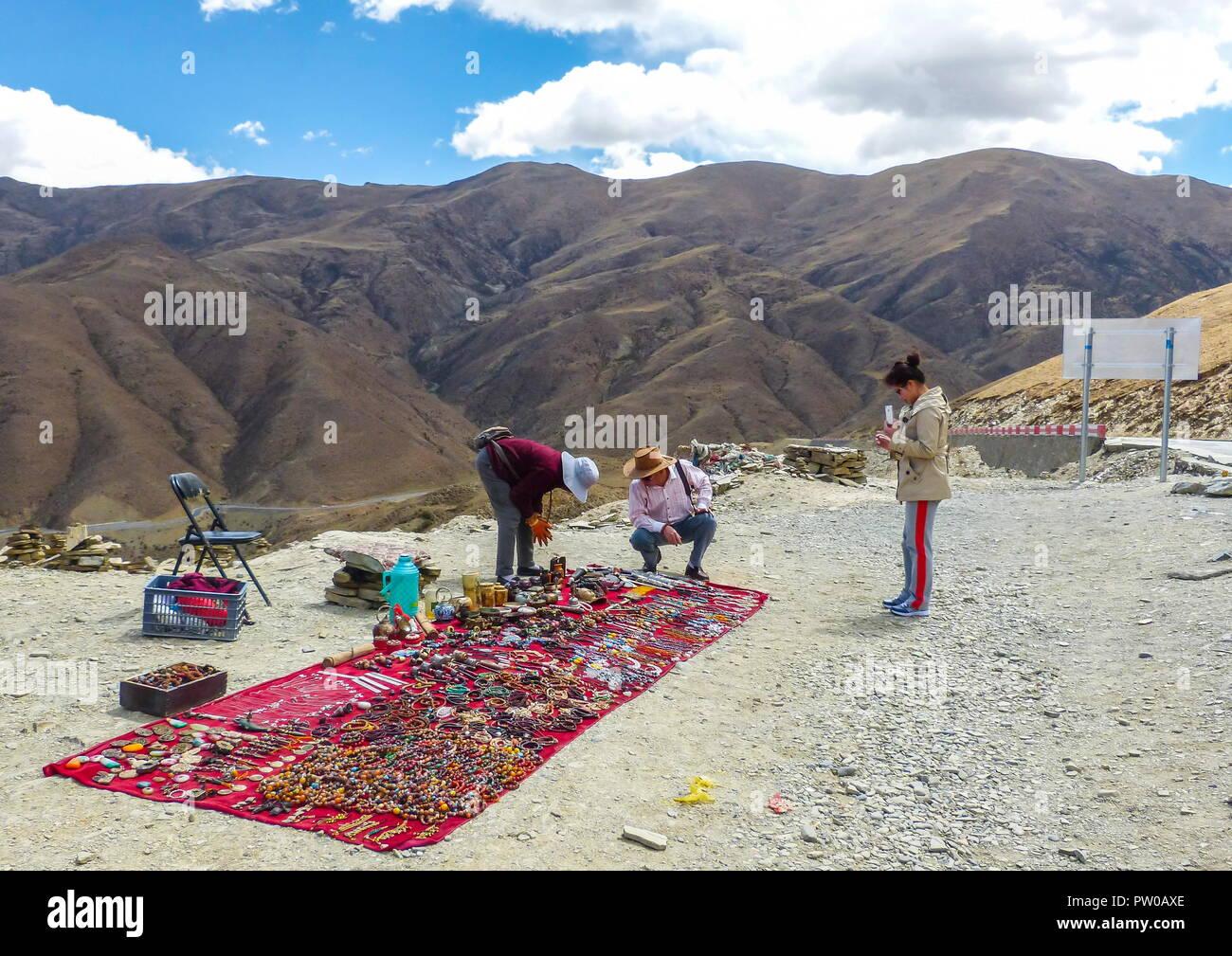 Venditore a vendere pietre tibetano, perline e negozio di souvenir lungo il passaggio di Kampala di servire i clienti sulla strada per il lago Yamdrok. Immagini Stock