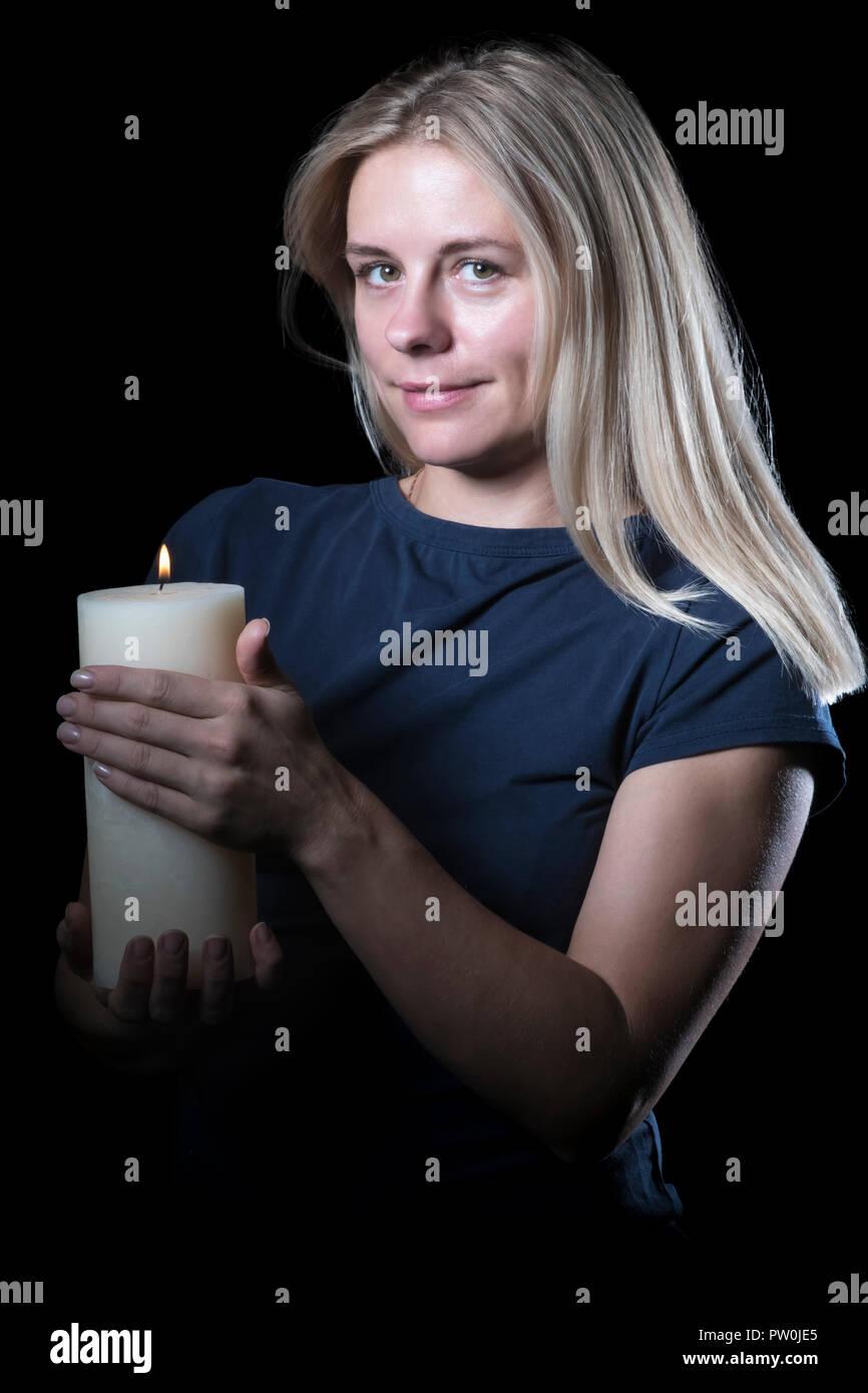 Donna con una candela di notte Foto Stock