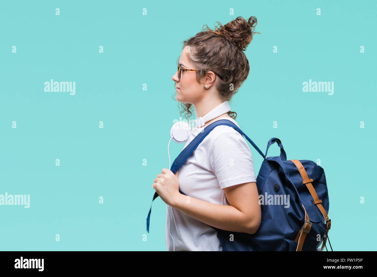 Bruna giovane studente ragazza indossando uno zaino e cuffie su sfondo  isolato guardando al lato 4eafe7e4b625