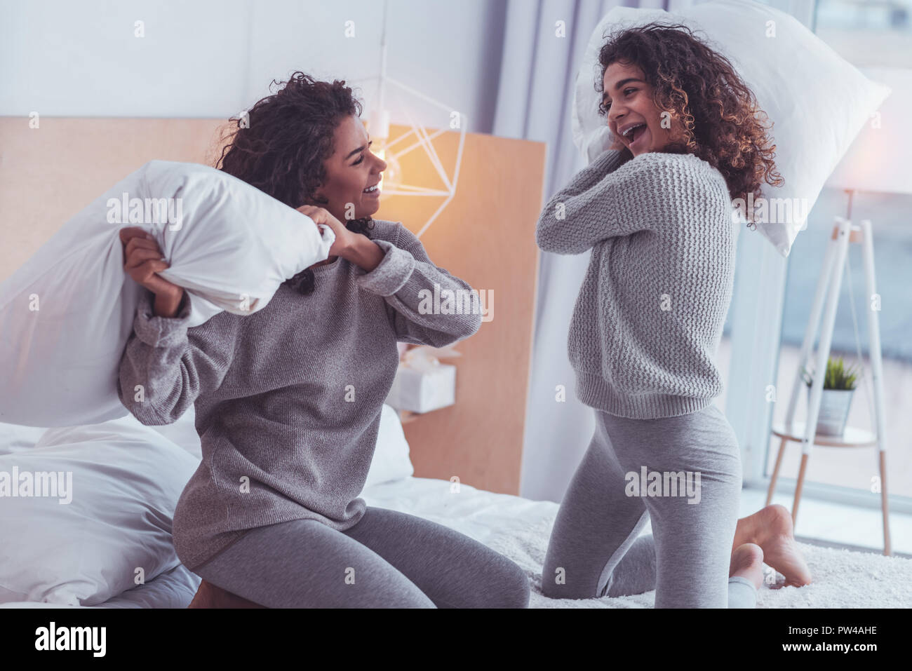 Felice fratelli sensazione allegro pur avendo battaglia cuscini Immagini Stock