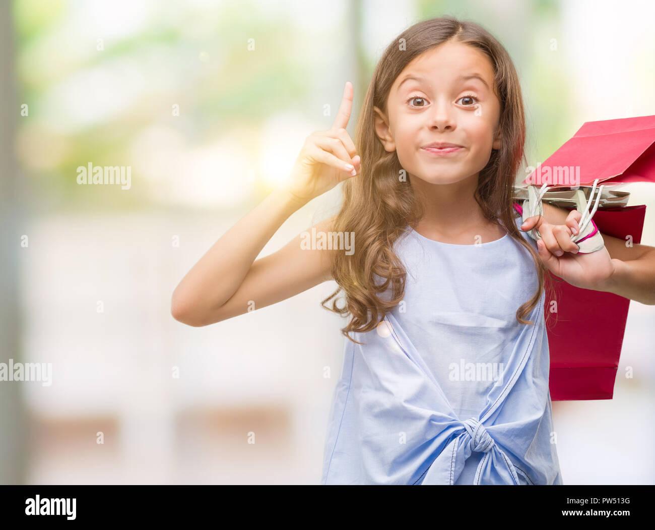 a1693c80035c Bruna ragazza ispanica holding shopping bags sorpreso con un idea o domanda  puntare il dito
