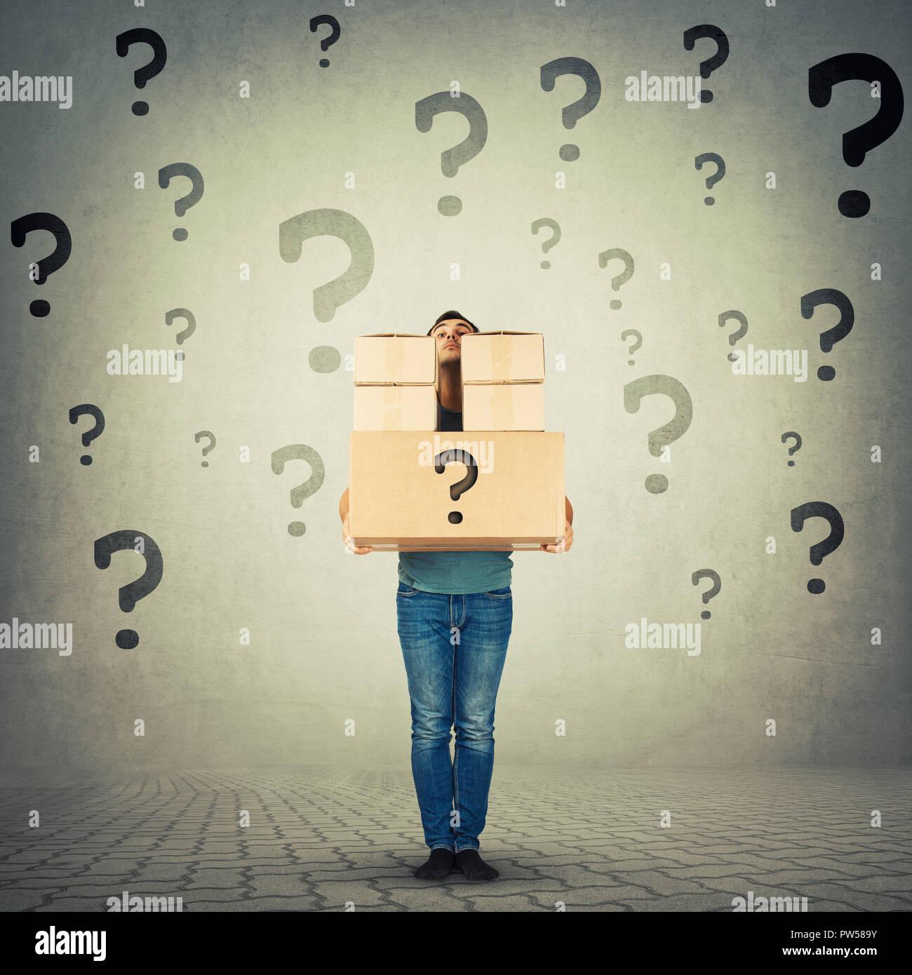 A piena lunghezza Ritratto di confuso giovane uomo che porta pesante pacchetti nascosti dietro la pila di scatole con punti interrogativi intorno a. Corriere nascondendo identità di Immagini Stock