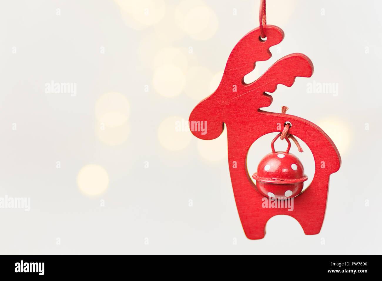 Legno ornamento di Natale cervi rossi con campana appesa su sfondo bianco con golden garland bokeh luci. Colori pastello. Magica atmosfera di vacanza. Cl Immagini Stock