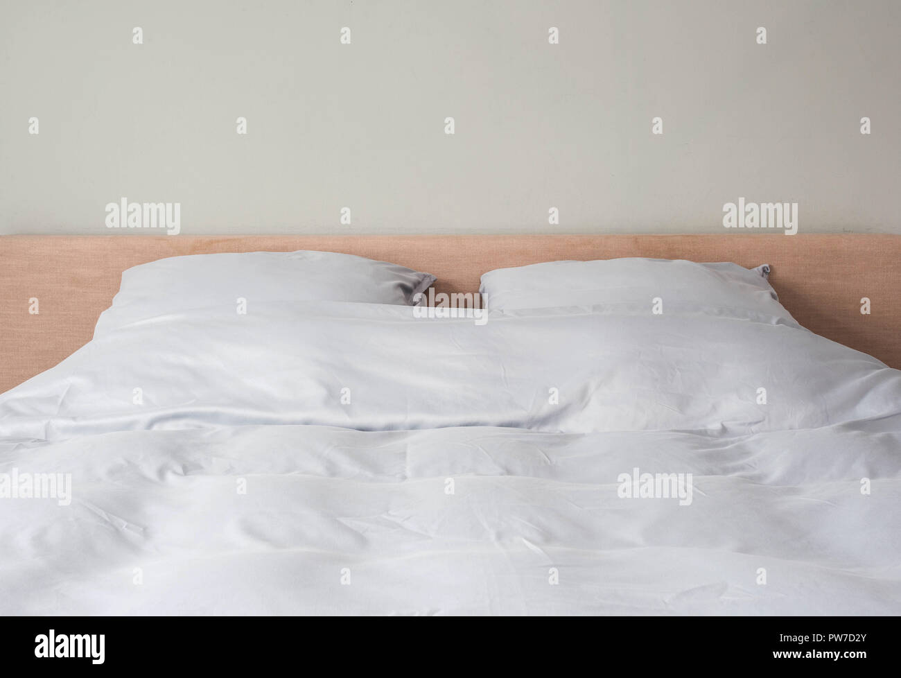 Il letto fatto con bianco pulire i cuscini e le lenzuola in camera. Close-up. Immagini Stock