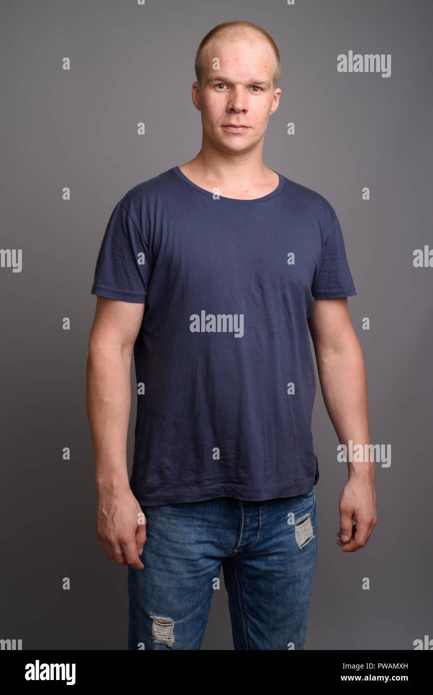 Uomo calvo indossando maglietta blu contro uno sfondo grigio Immagini Stock