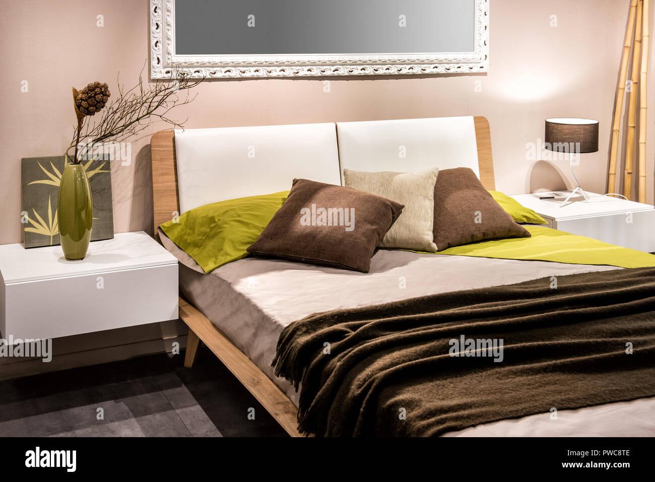 Camera da letto interno con quattro cuscini sul letto e specchio sulla parete Immagini Stock
