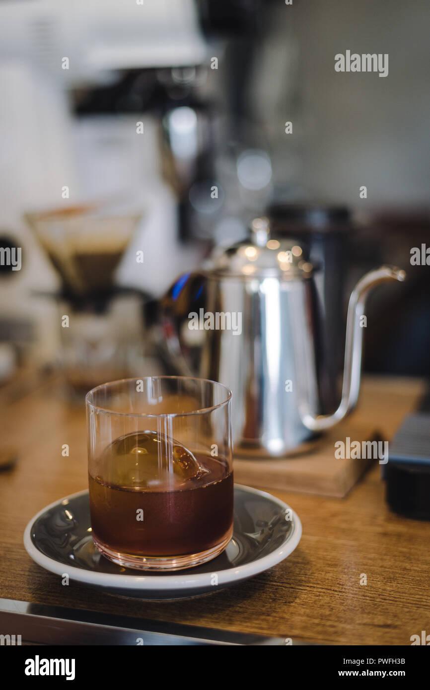 Iced caffè antigoccia con ghiaccio palla in vetro con blur coffee bar scena Immagini Stock