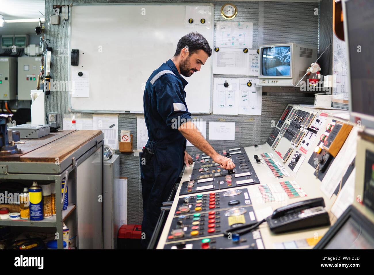 Marine ufficiale di macchina lavora nella camera del motore Immagini Stock
