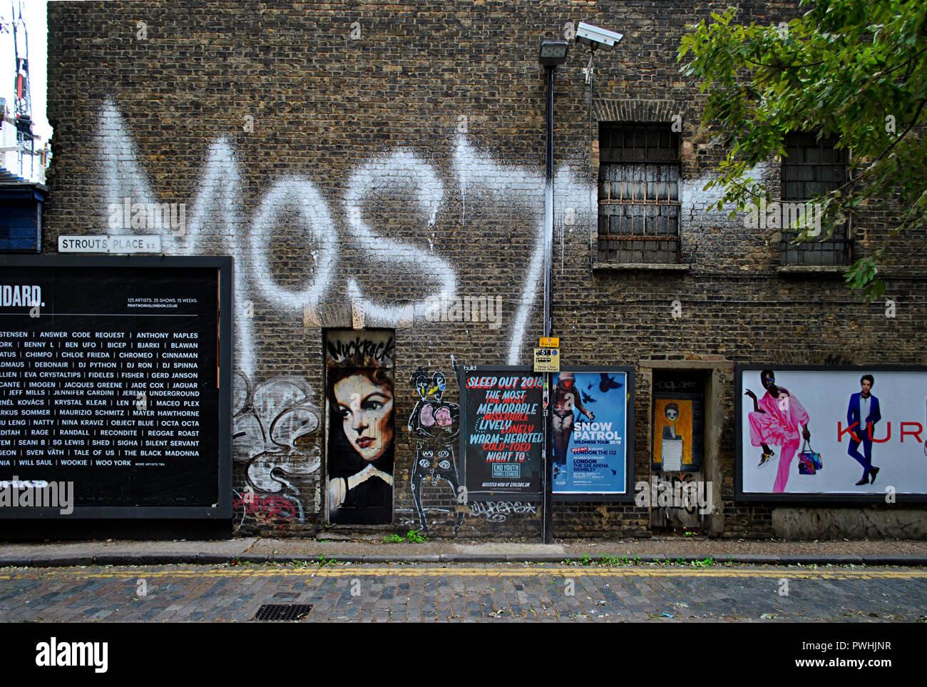 GRAFFITI, Arte di strada,BILL adesivi & annunci sullo stesso VICTORIAN East London Wall. Foto Stock