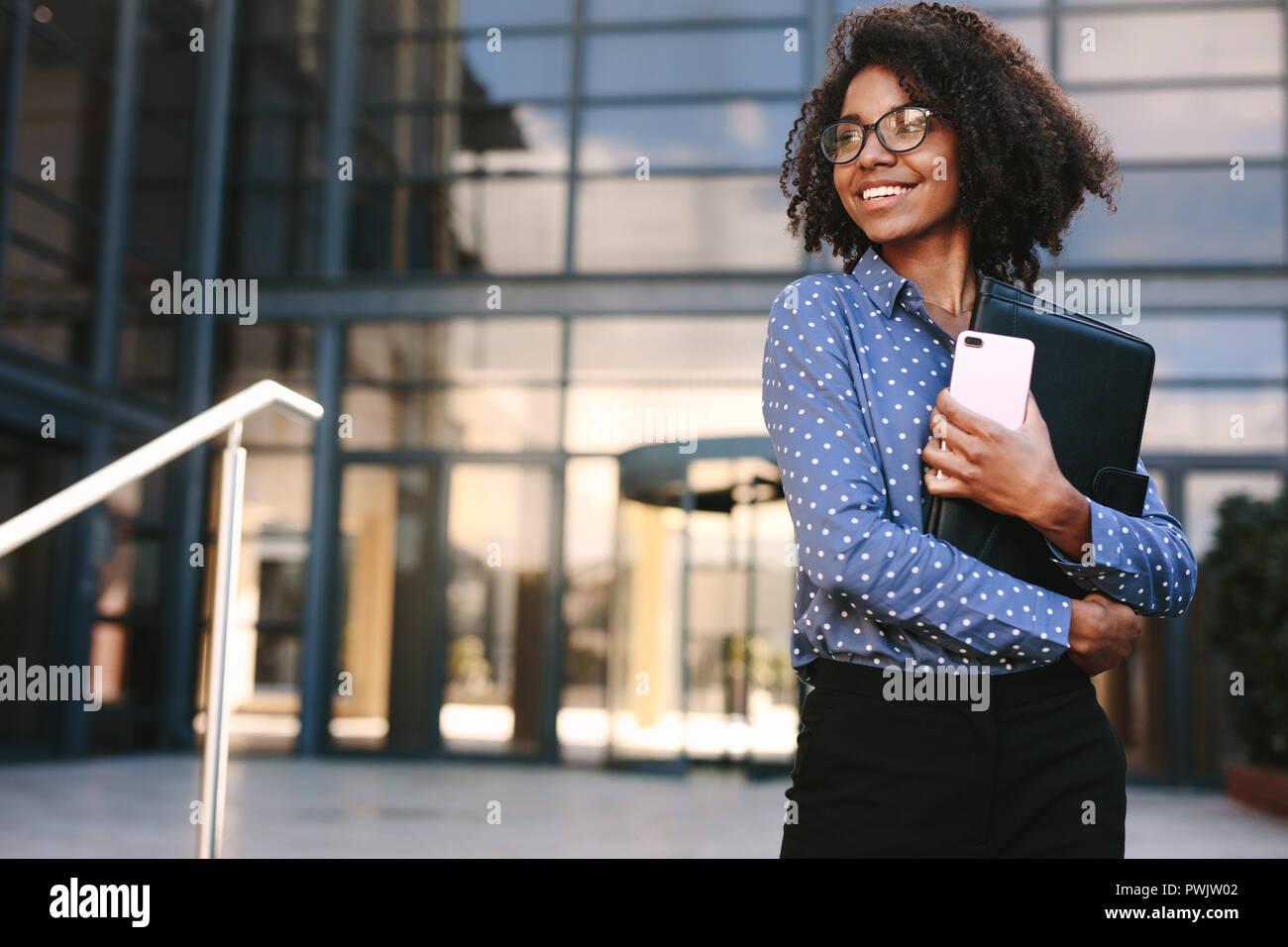 Donna con il telefono cellulare e il file aperto in piedi e guardando lontano. Business Woman Standing al di fuori di un edificio per uffici. Immagini Stock
