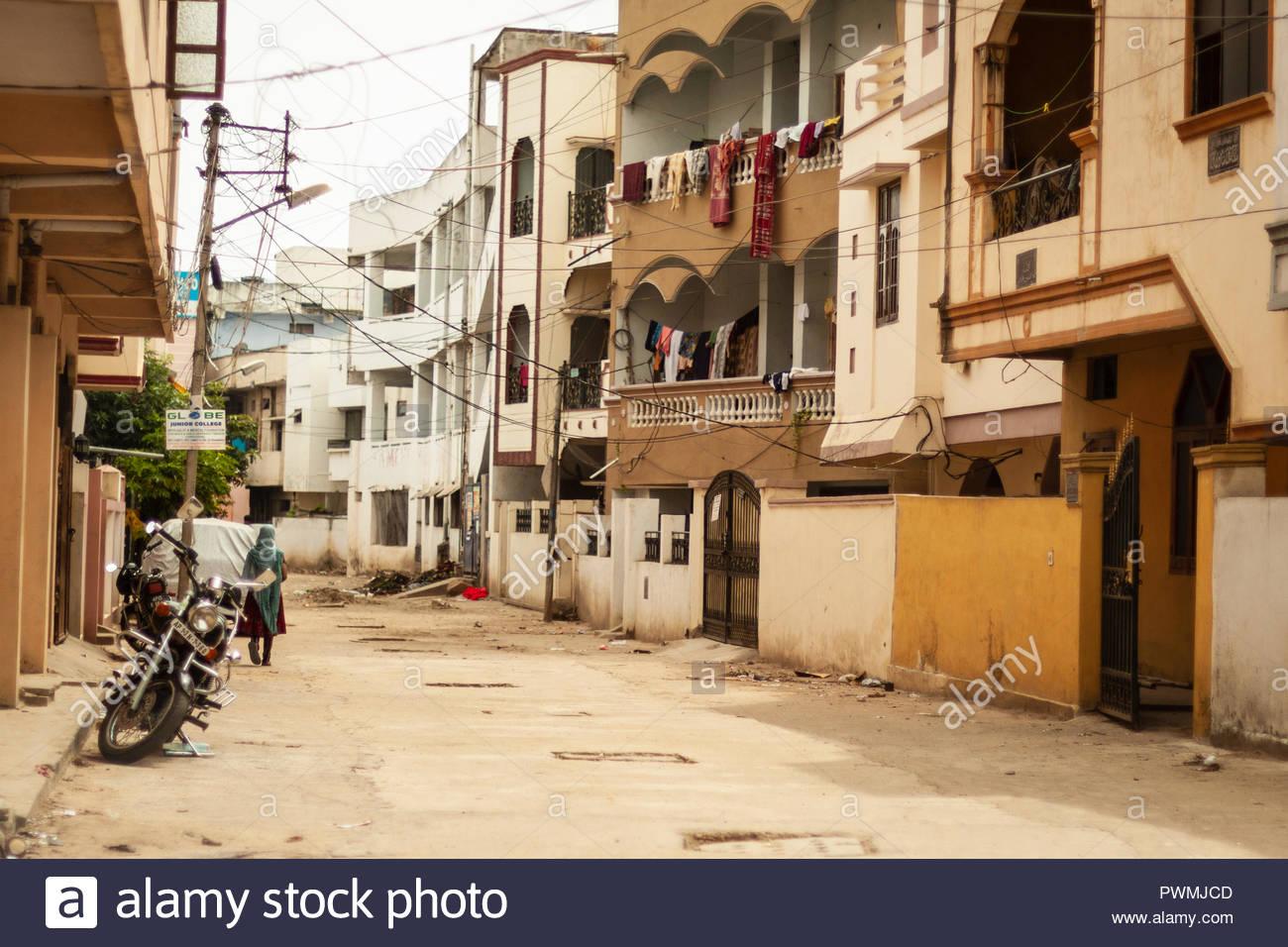 La donna cammina per strada residenziale nella città vecchia di Hyderabad, India Immagini Stock