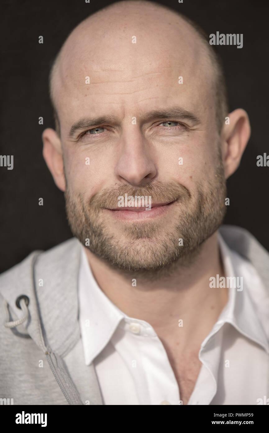 Ritratto di un uomo bello con una leggera barba e capelli rasata. Immagini Stock