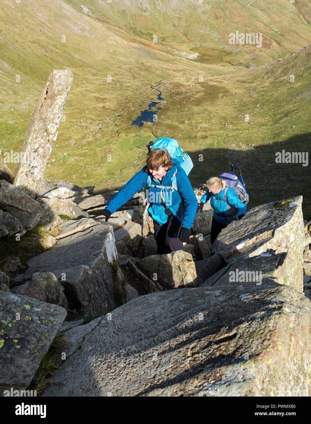 Due persone di scrambling Swirral sul bordo, Helvellyn, Lake District, Cumbria, Regno Unito. Foto Stock