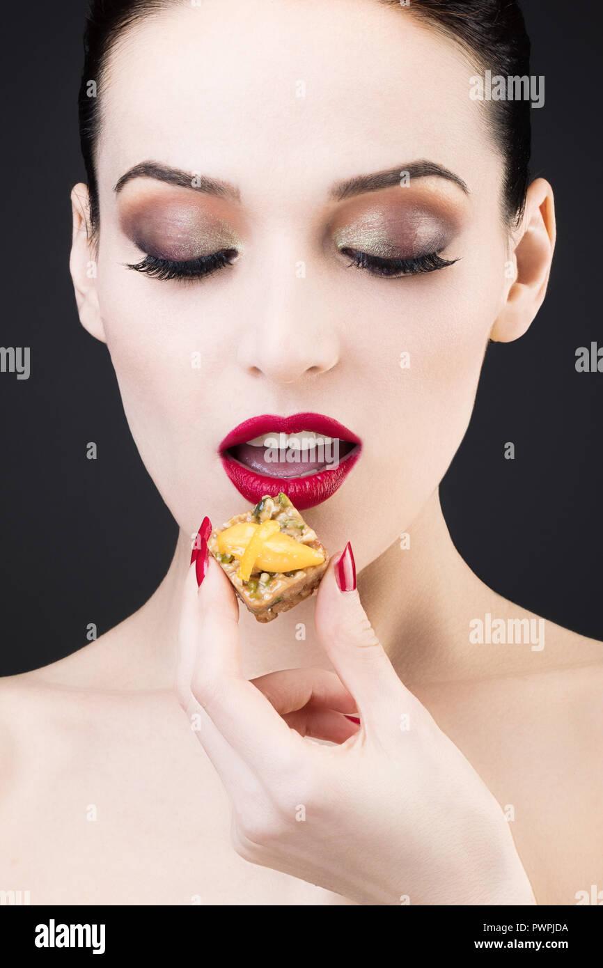 Girato a tenuta di una ragazza godendo di una torta al limone Immagini Stock